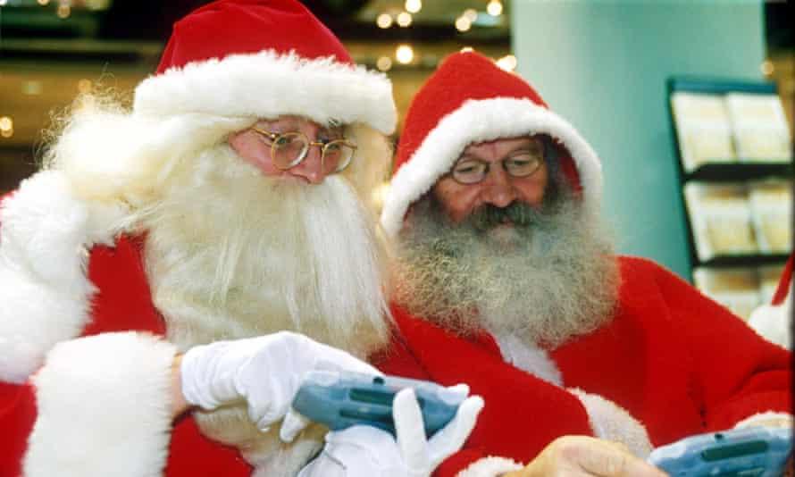 Two Santas playing computer games.