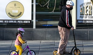 A young child and man wearing masks are seen riding a bicycle and scooter in Southbank, Melbourne.