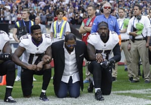 Ravens wide receiver Mike Wallace, former player Ray Lewis and linebacker CJ Mosley lock arms and kneel on the Wembley sidelines.