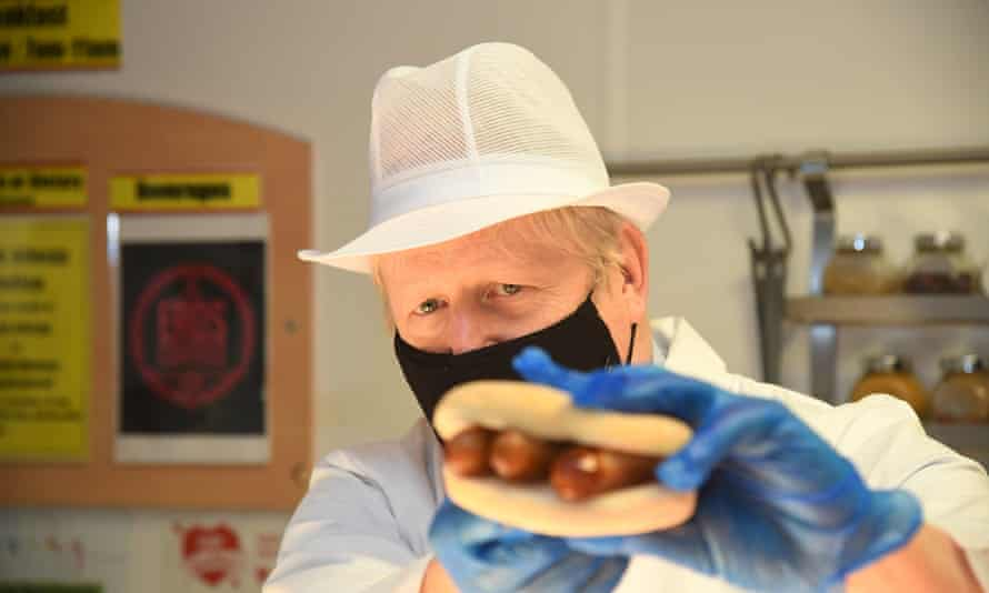 Boris Johnson holding up a sausage filled roll during a visit to Royal Berkshire hospital, Reading, last year.