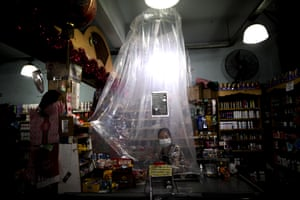 A supermarket cashier waits for customers behind a makeshift plastic curtain as a precaution against coronavirus in Buenos Aires, Argentina