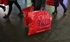 A shopper carries bags from Next