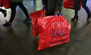 Shoppers carry Next sales bags on Boxing Day