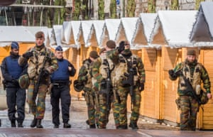 Belgian Army soldiers and policemen patrol near Christmas stalls in the centre of Brussels