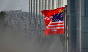 Chinese and US national flags flutter at the entrance of a company office building in Beijing