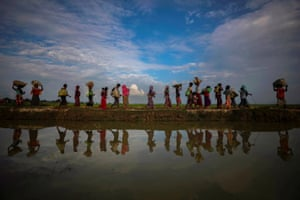 Rohingya refugees are reflected in rain water along an embankment next to paddy fields after fleeing from Myanmar into Palang Khali, near Cox's Bazar, Bangladesh, 2 November 2017