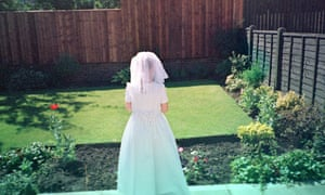 A woman dressed for a wedding in front of a perfectly mown lawn.