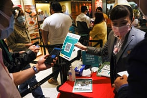 """A staff member holds a QR code for the """"LeaveHomeSafe"""" Covid-19 contact-tracing app to consumers at a restaurant in Hong Kong, China, on 18 February, 2021."""
