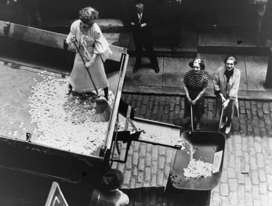 Women sweeping coins from a truck into a wheelbarrow