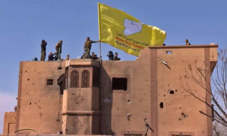 US-backed Syrian Democratic Forces (SDF) fighters raise their flag on a building in Baghuz.