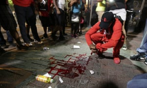 A man squats near a pool of blood after a man was injured during a protest of Tuesday's fatal police shooting of Keith Lamont Scott in Charlotte.