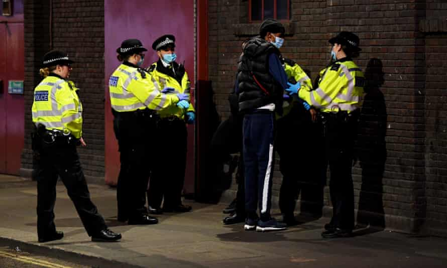 A man is stopped and searched by police in Soho, London