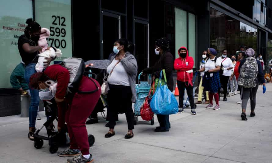 People wait in line to get care packages with food donations from the Food Bank for New York City in Brooklyn on 15 May.