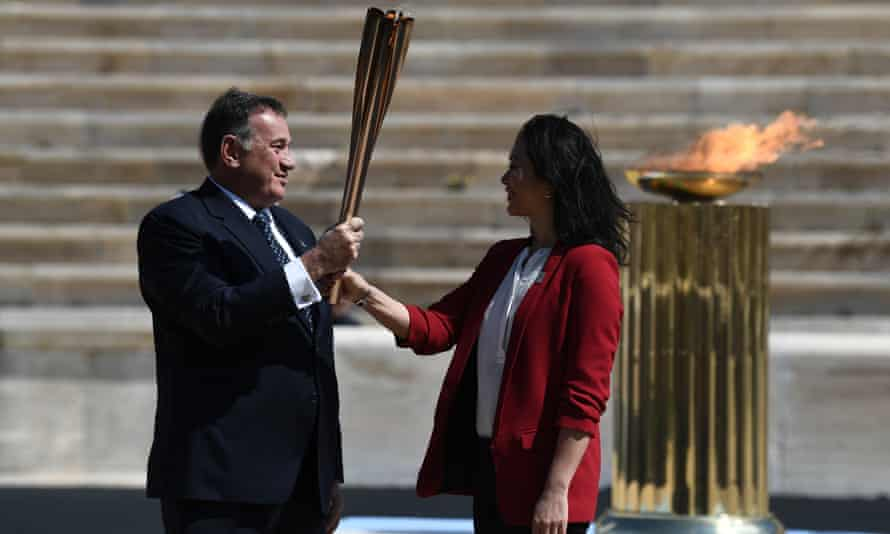 The Greek sports minister, Spyros Capralos, handed the Olympic torch over to the former Japanese swimmer Imoto Naoko during a ceremony in Athens on Thursday despite the coronavirus crisis