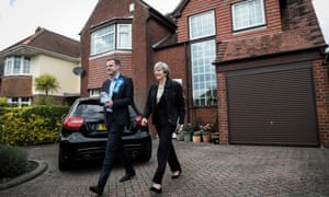 Theresa May walks through a garden as she walks with Paul Holmes in Southampton.