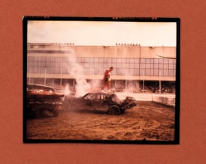 Last man standing: the winner of a demolition derby in Nebraska stands on the wreck of his car. By Gregory Halpern.