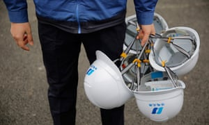 A worker holds several white safety helmets with Chinese writing on them.
