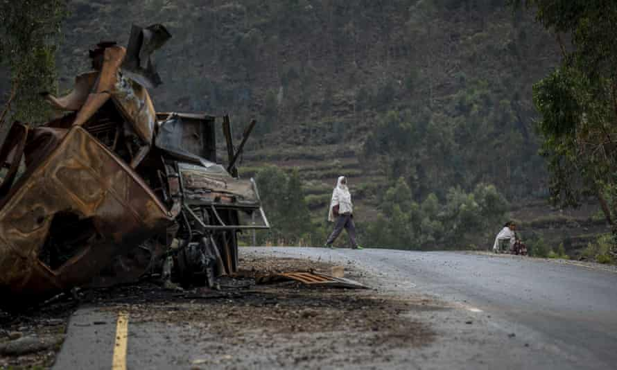 A man crosses near a destroyed truck on a road leading to the town of Abi Adi, in the Tigray region of northern Ethiopia