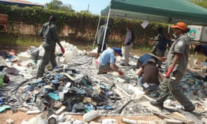 Dhimurru rangers sort through broken sandals, cigarette lighters, plastic bottles, bags, piles of netting, and fragments of plastic worn ragged by the sea