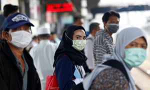 People wear precautionary facemasks while travelling through Tanah Abang station in Jakarta, Indonesia.