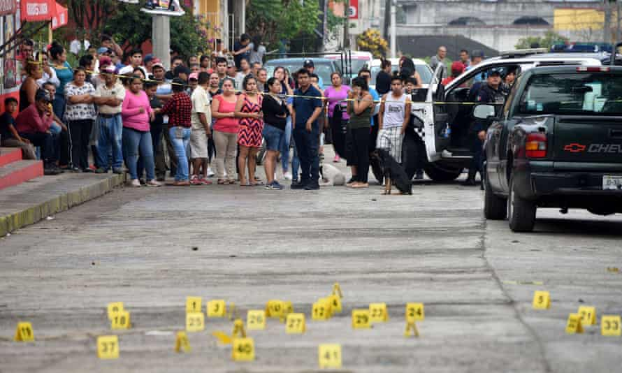 People stand near bullet casings at a crime scene after a shootout in Veracruz. Mexico is grappling with a record murder rate.