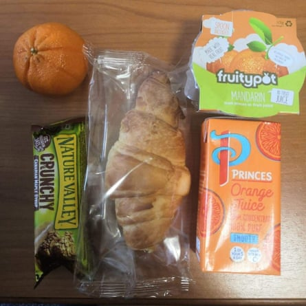 An image of a lunch pack delivered to self-isolating Edinburgh students on campus. It includes an orange; a drink; a croissant; an oat bar; and a jelly pot.