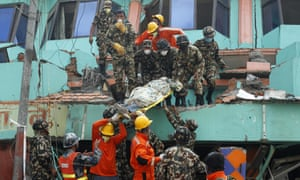 Nepalese and Indian rescue teams remove a body from the collapsed Sitapyla church in Kathmandu