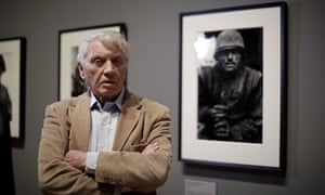 Don McCullin in 2019, next to his 1968 photograph of a US marine in Vietnam.