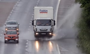 A lorry drives through a puddle on the M20 in Ashford, Kent
