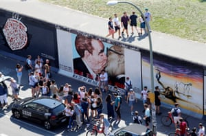 Tourists are seen in front of graffiti depicting former Soviet leader Leonid Brezhnev kissing his East German counterpart Erich Honecker along the East Side Gallery.