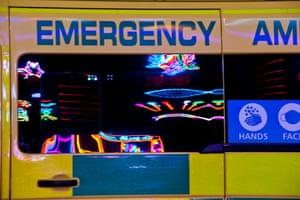 An ambulance window reflects illuminations