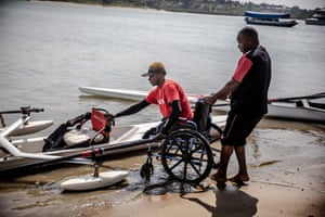 Asiya Mohammed is helped to move with her wheelchair by a coach.