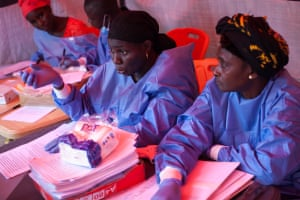 Wearing protective clothing, Hadja Kakoro Sogbe and Halimatu Diallo, members of team nine, go through an extensive procedure to get consent from participants in the vaccine trial