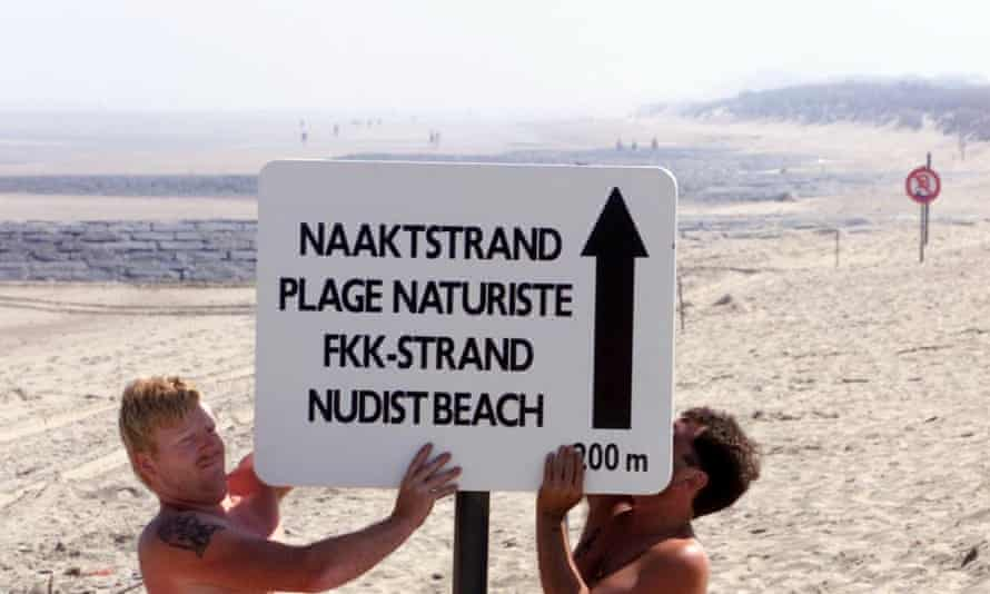 Workers put up a sign for a nudist beach in Bredene, Belgium