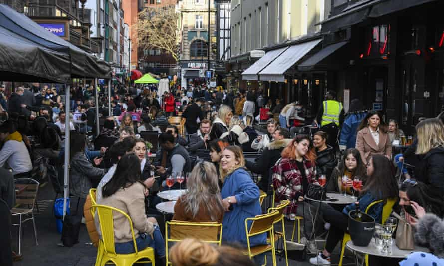 People sit outside cafes and pubs in Soho, central London.