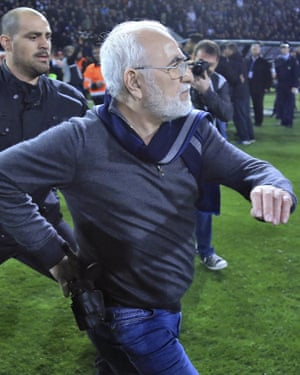 Ivan Savvidis enters the pitch for a second time, carrying what appears to be a pistol.