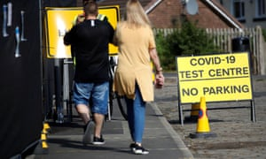 People arrive at a walk-in test facility following the outbreak of coronavirus in the Farnworth area of Bolton.
