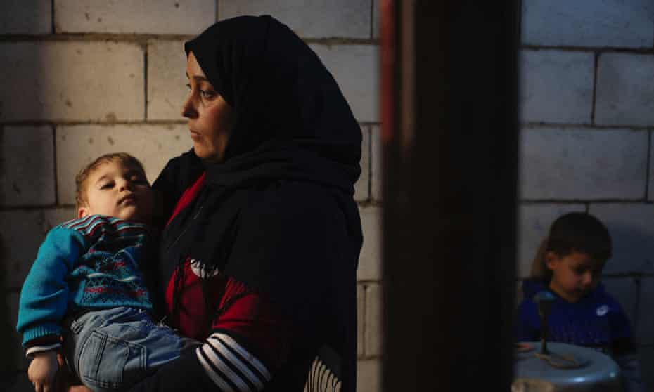 Farzad Uaz holds her two year old son, Moaz who has spina bifida, in the unfinished apartment they are renting in Zahlé, Lebanon, 23 March 2021. The family left Syria after Farzad's husband was released from prison, where he was tortured.
