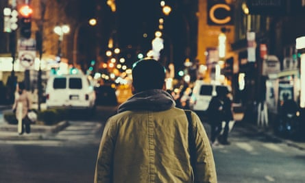 Rear View Of Man Walking On Illuminated Street Amid Buildings
