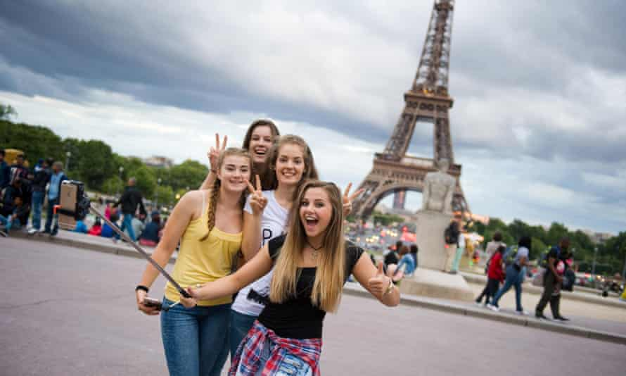 Girls with selfie stick in front of the Eiffel Tower in Paris