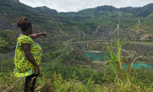A pregnant woman oints to the site of the Panguna mine in Bougainville