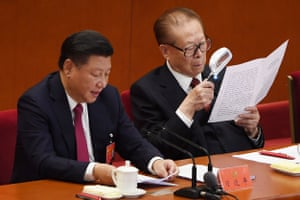 Chinese President Xi Jinping speaks as former president Jiang Zemin reads a document during the closing session. Jinping's name was added to the Communist Party's constitution