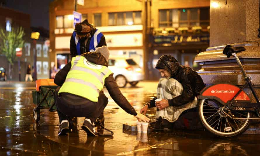 Volunteers in London step in to give food to a homeless man, last November