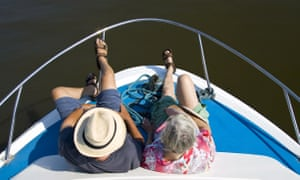 An older man and a woman on the bow of a boat
