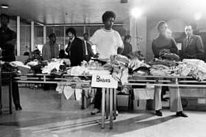 Members of the Black Panther Party stand behind tables ready to distribute free clothing to the public in New Haven, Connecticut, 1969.