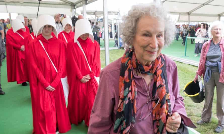 Ten handmaids escort Margaret Atwood around Britain's Hay literary festival in May.