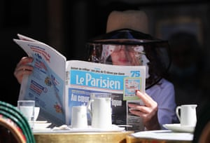 A customers keeps up with the news while having coffee at Cafe de Flore in Paris