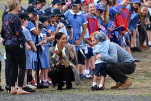 Prince Harry and Meghan Duchess of Sussex hug Luke Vincent, aged 5 from Buninyong Public School, at Dubbo Airport.