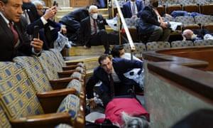 Orang-orang berlindung di galeri House saat para perusuh mencoba masuk ke House Chamber di Capitol pada 6 Januari.  Sidang pemakzulan Trump akan diadakan di tempat yang sama dengan kekerasan yang terjadi.