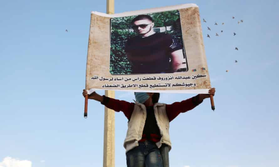 A demonstrator raises a portrait of Abdullakh Anzorov during a protest calling for a boycott of French goods in Idlib in October 2020. The writing below the portrait reads in Arabic: 'The knife of Anzorov cut the head of that who offended the Prophet of God, their armies are only able to cut the road of the poor.'